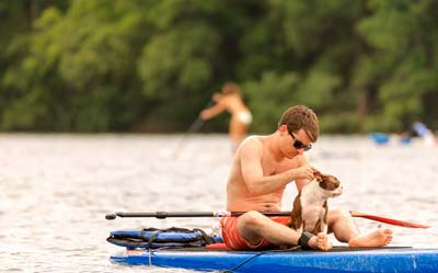 Man and Boston terrier sitting on a blue paddle board in the middle of a lake.