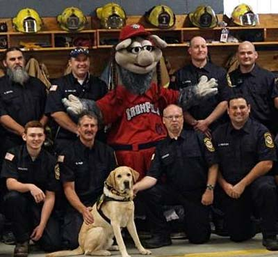 Yellow lab sits in front of a group of fireman and a mascot as they pose for a picture.