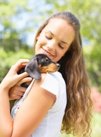 Girl in white t-shirt with black Dachshund puppy on her shoulder.